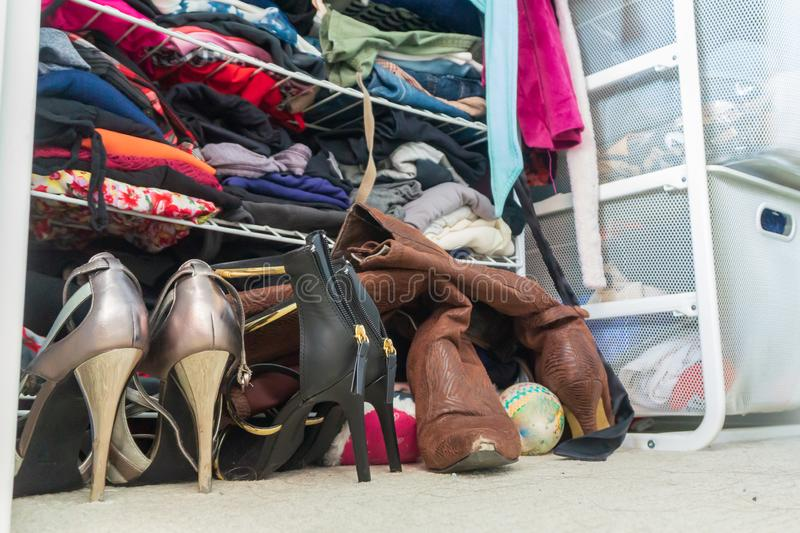 Woman`s closet with high heel shoes, stacked, folded clothes on shelves and part of robes hanging. Depicting closet organization,. Time to donate clothes royalty free stock photos