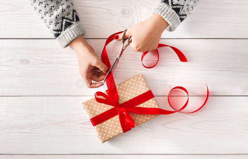 Woman& x27; s entrega o envolvimento da fita do vermelho do iwith do presente do feriado do Natal fotos de stock royalty free
