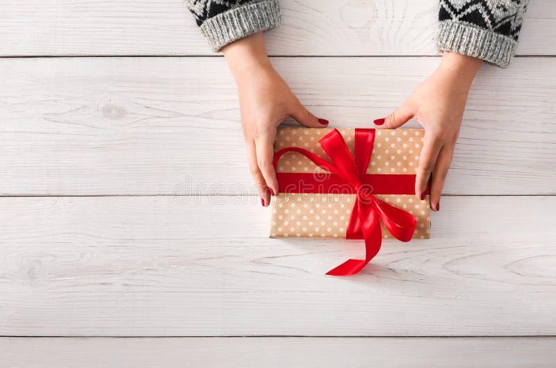 Woman& x27; s entrega o envolvimento do feriado do Natal atual com fita vermelha imagem de stock
