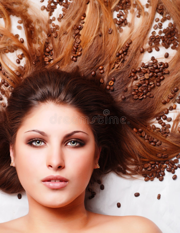 Woman's face with coffee beans stock image