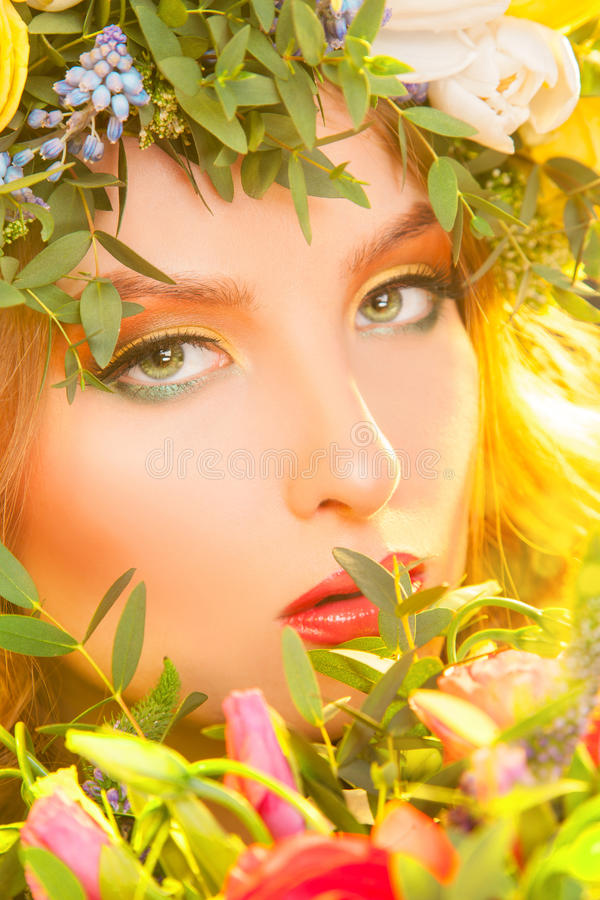 Woman's face with make up in flowers. In studio stock photo