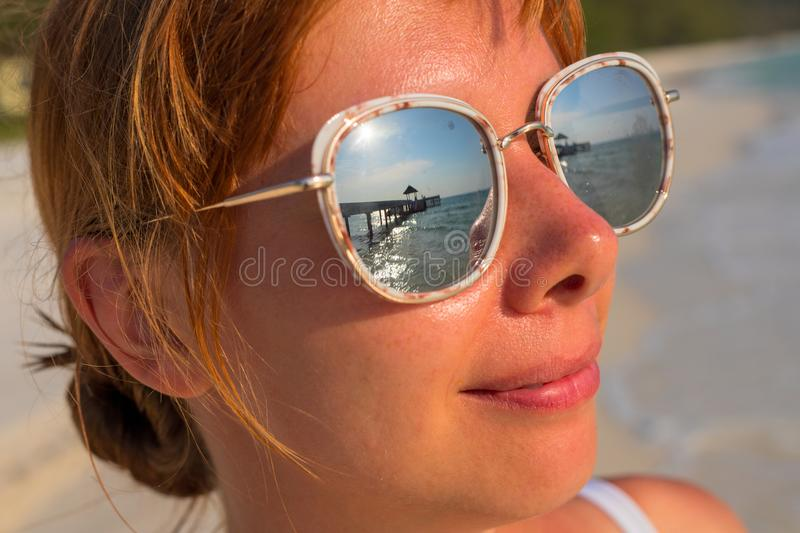 Woman`s face in mirror sunglasses with sea reflection. Seaside vacation banner template. royalty free stock photos