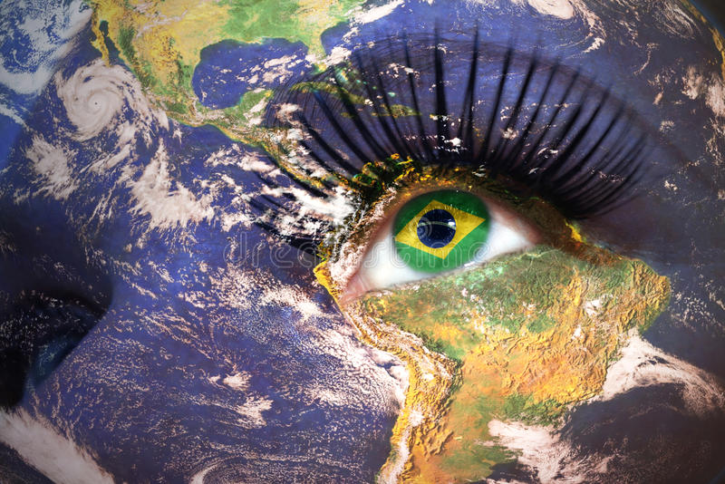 Woman`s face with planet Earth texture and brazilian flag inside the eye. royalty free stock image
