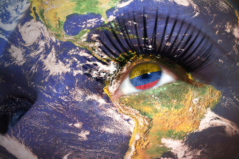 Woman`s face with planet Earth texture and colombian flag inside the eye. royalty free stock photo