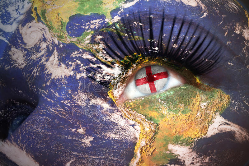 Woman`s face with planet Earth texture and english flag inside the eye royalty free stock images