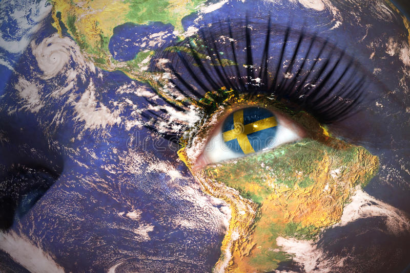 Woman`s face with planet Earth texture and swedish flag inside the eye. royalty free stock photo
