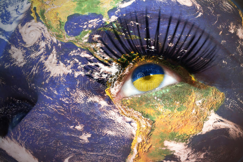 Woman`s face with planet Earth texture and ukrainian flag inside the eye. stock photography