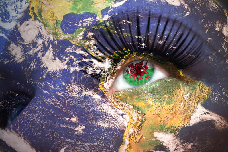 Woman`s face with planet Earth texture and welsh flag inside the eye. royalty free stock photo
