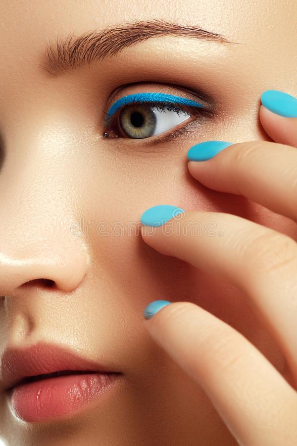 Woman`s face with vivid make-up and colorful nail polish. Cosmetics and makeup. Woman`s face with vivid make up and colorful nail polish. Colourful nails stock images