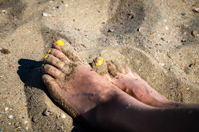 Woman`s feet on a sea sand on the beach stock photo
