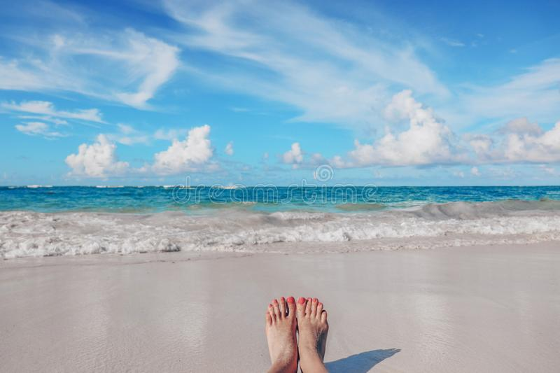 Woman`s feet on the tropical Caribbean beach. Ocean and blue sky. In Dominican Republic stock photography