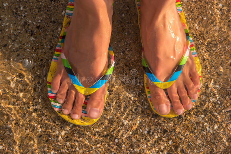 Woman`s feet wearing flip flops. Transparent water and sand. At the ocean shore. Trip to a tropical island royalty free stock images