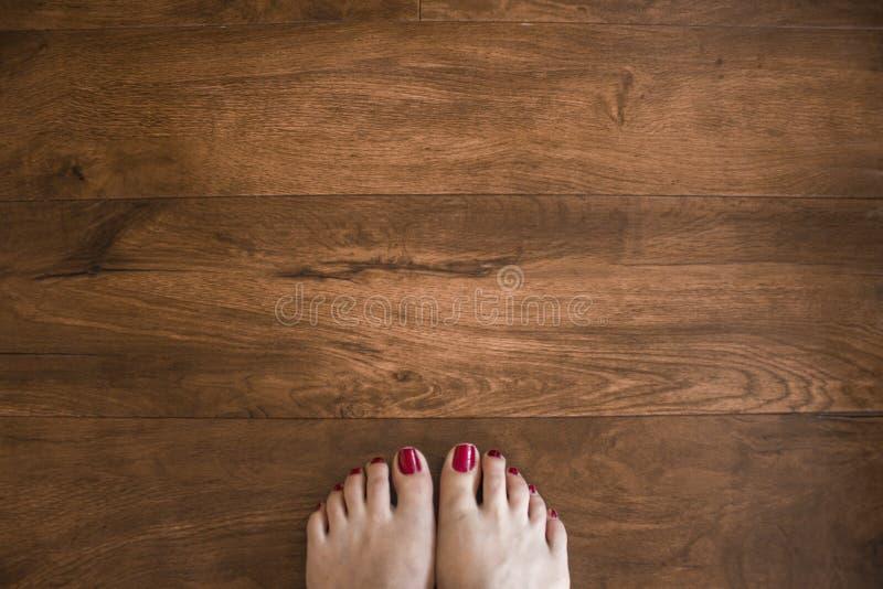 Woman`s feet on wood floor stock photos