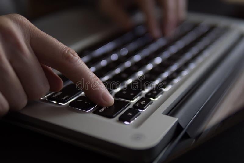 Woman`s finger pressing delete button on laptop.  royalty free stock photo