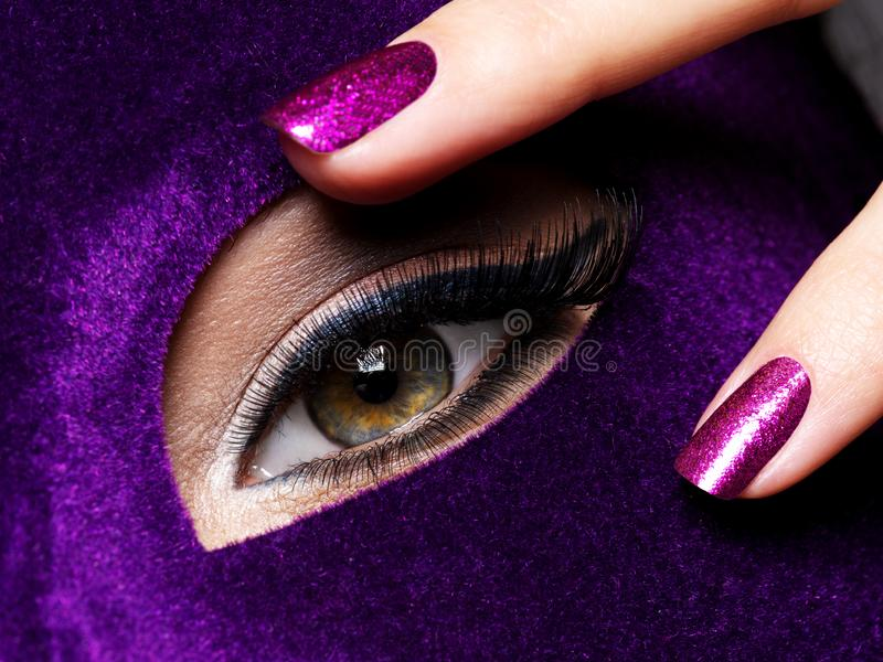 Woman`s fingers, purple nails about eye. Macro photo. Woman`s fingers with purple nails about eye. Macro photo royalty free stock photography