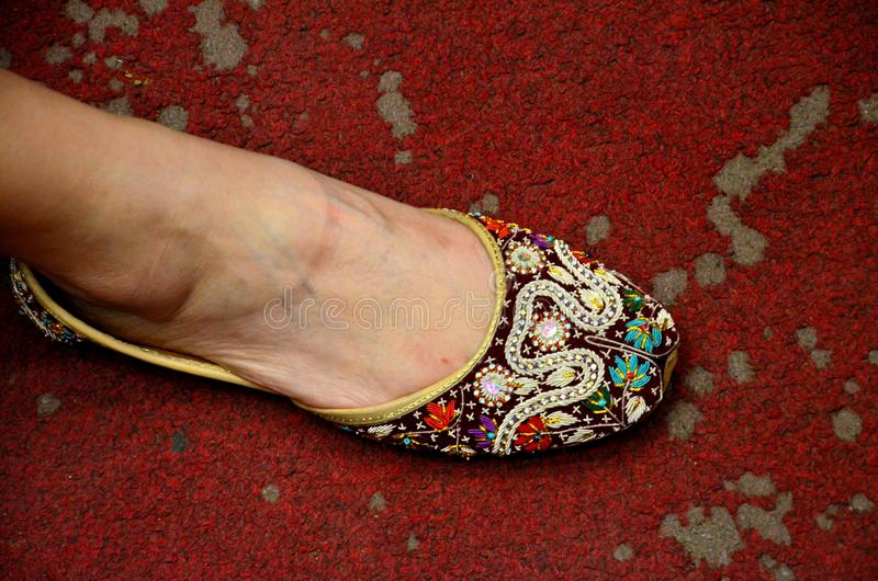 Woman`s foot in traditional Pakistani leather designed hand made khusa shoe Karachi Pakistan royalty free stock photo