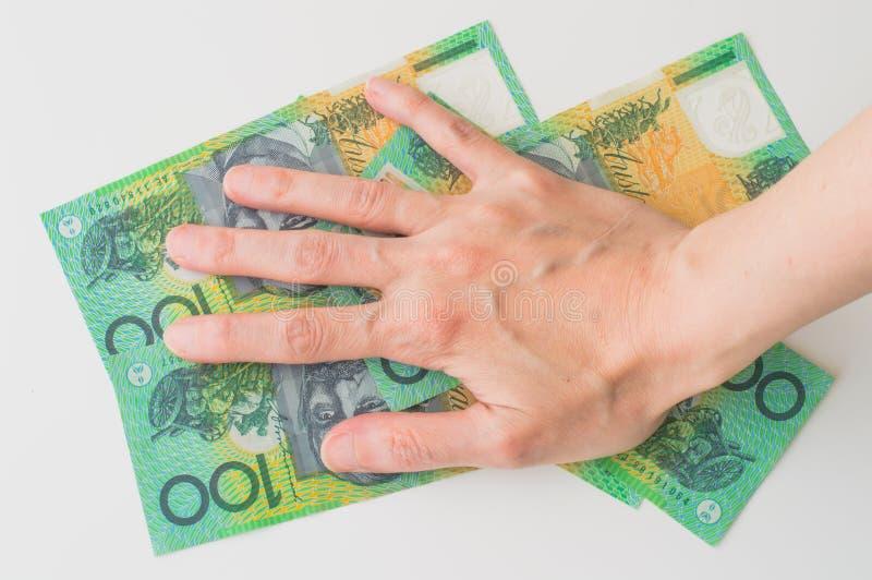 Woman's hand on Australian Dollar. Banknote royalty free stock photo