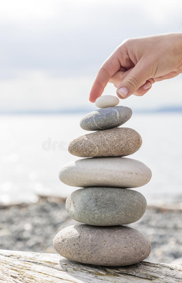 Woman& x27;s hand balancing a stack of stones on a driftwood beach log. royalty free stock photos