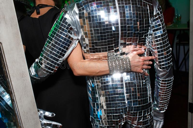 A woman`s hand with a beautiful bracelet. Is hugging a man in a disco suit, covered with small mirrors stock photos