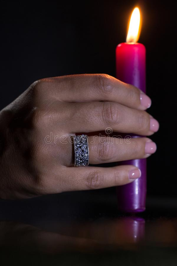 A woman`s hand with a beautiful silver ring holds a lit purple candle stock photography
