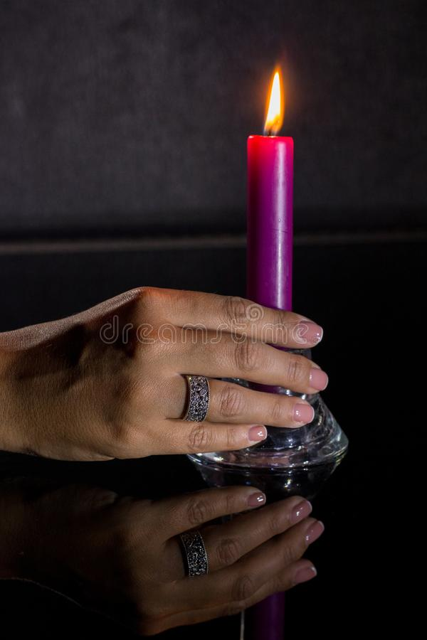A woman`s hand with a beautiful silver ring holds a lit purple candle royalty free stock image
