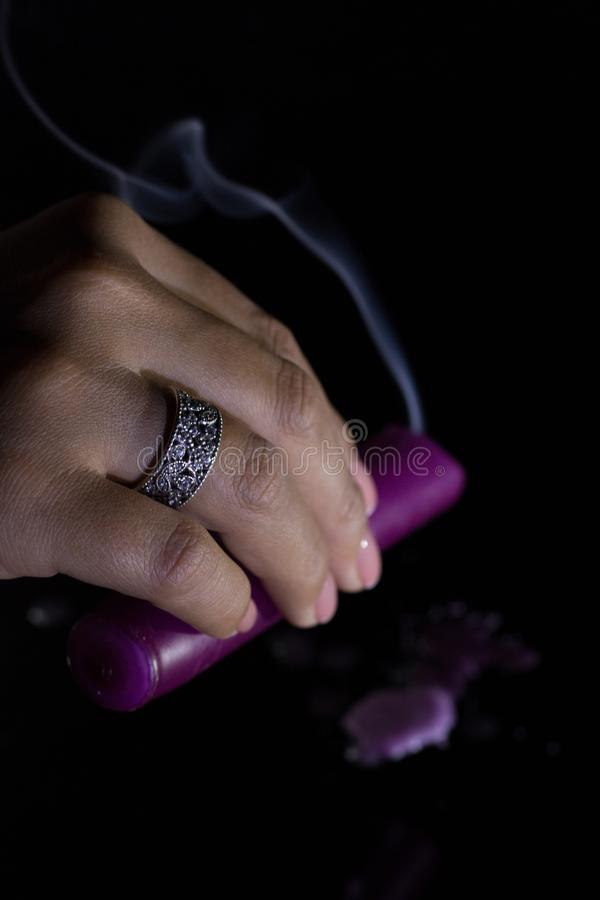 A woman`s hand with a beautiful silver ring holds a smoking purple candle.  stock image