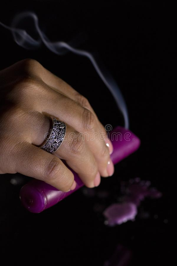 A woman`s hand with a beautiful silver ring holds a smoking purple candle.  royalty free stock images