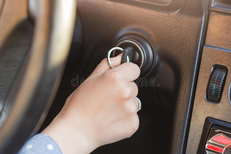 Woman`s hand on car`s key, tries to start engine, turn on key in keyhole, auto`s panel and wheel in background. Key inserted in lo stock images
