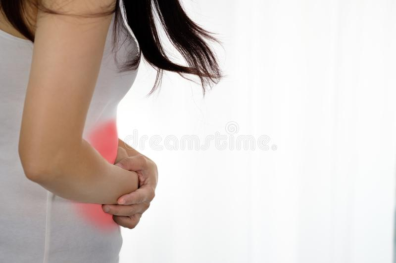 Woman& x27;s hand catching the waist. Because of abdominal pain stock photography