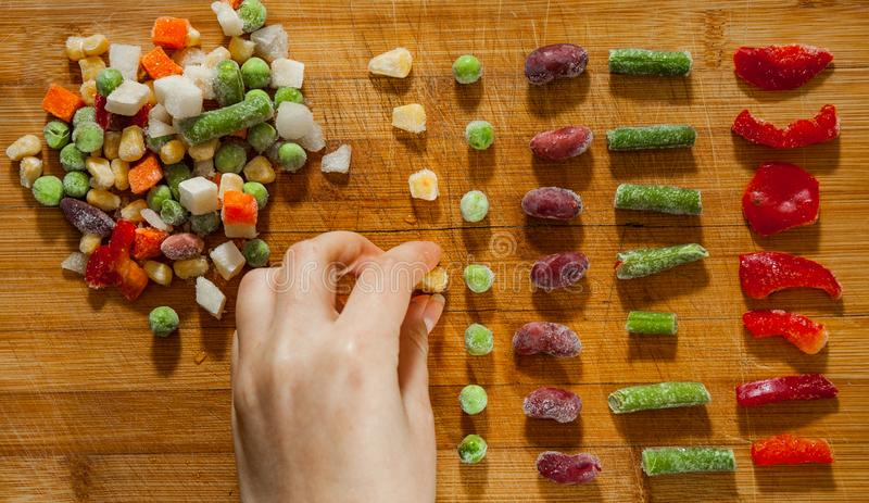 Woman`s hand collects even row of colorful Frozen mixed vegetables on a wooden background stock photos