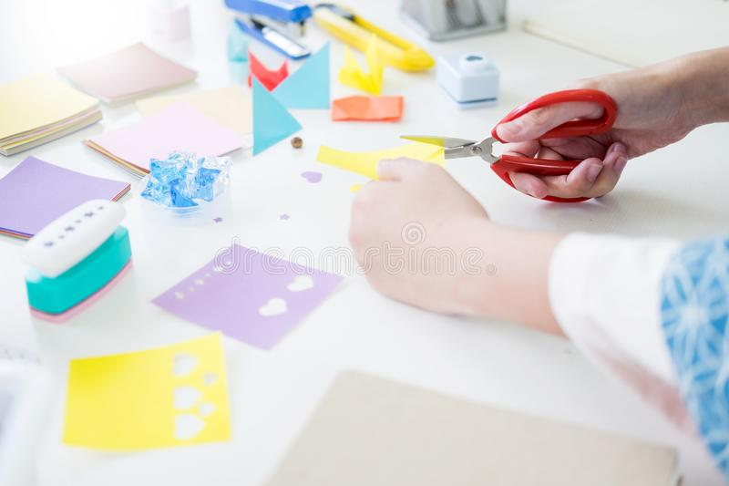 Woman`s hand cut paper Making a scrap booking or other festive d. Ecorations DIY accessories arrangement stock image