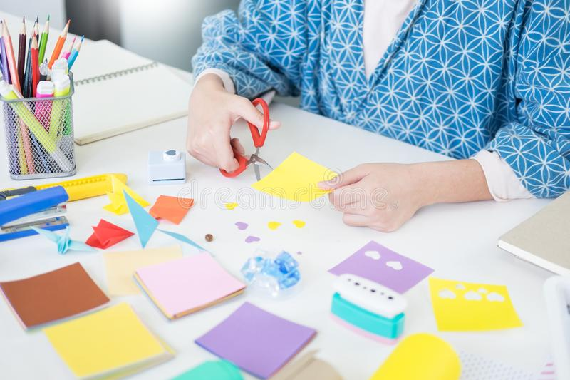 Woman`s hand cut paper Making a scrap booking or other festive decorations DIY accessories arrangement.  stock images