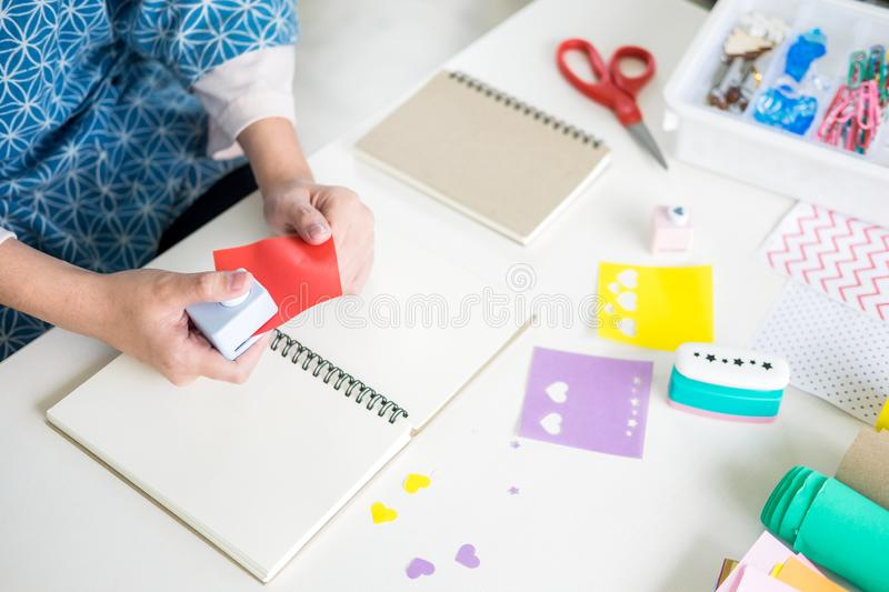 Woman`s hand cut paper Making a scrap booking or other festive decorations DIY accessories arrangement.  royalty free stock images