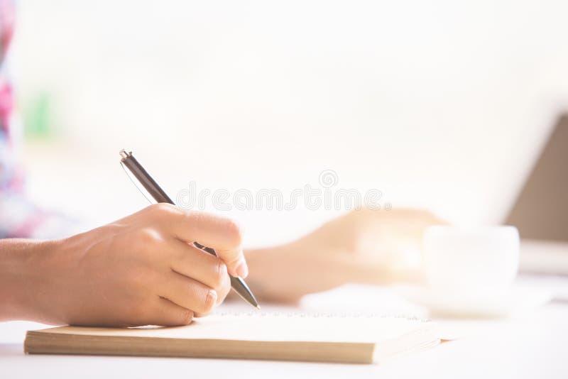Woman& x27; s hand die in blocnote schrijven stock afbeelding