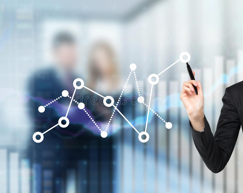 A woman's hand is drawing fluctuation of the financial chart. stock photo