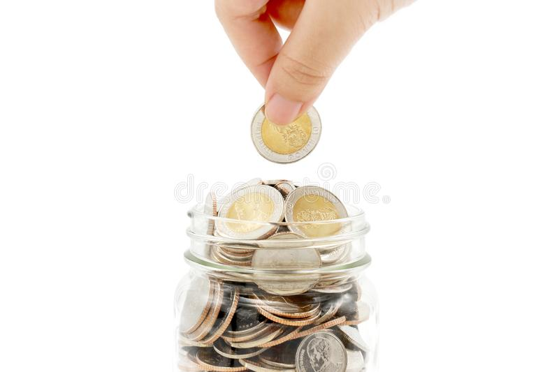 Woman`s hand dropping new ten Thai Baht coin into a glass jar full of coins. royalty free stock photos