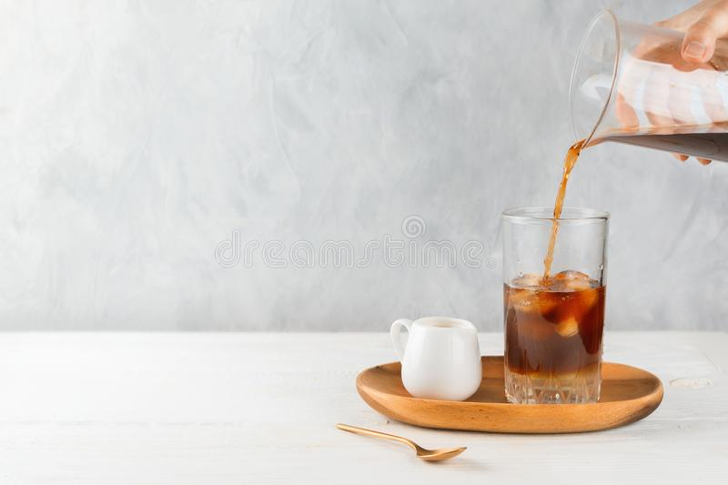 Woman`s hand dusting cocoa into vegan iced coffee in a tall glass on a wooden tray royalty free stock photo