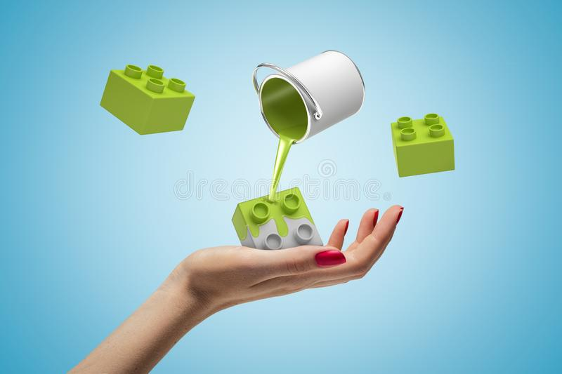 Woman`s hand facing up holding grey Lego brick, small can of green paint in air pouring paint on it, and two more bricks royalty free stock photos