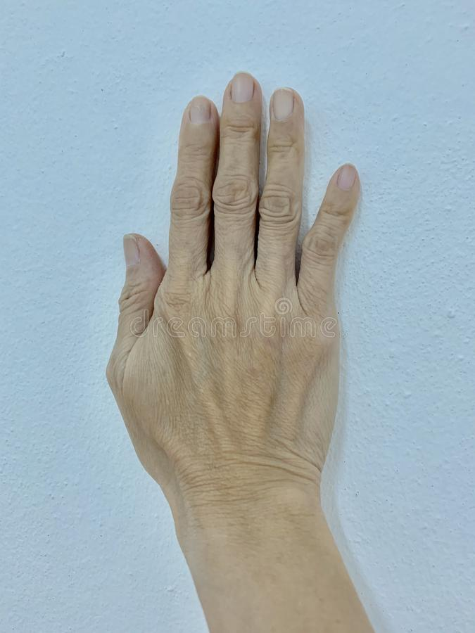 Woman's hand, fingers, little finger bend, cement wall stock photo