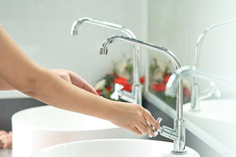The woman`s hand is going to open the faucet to wash hands. To m stock images