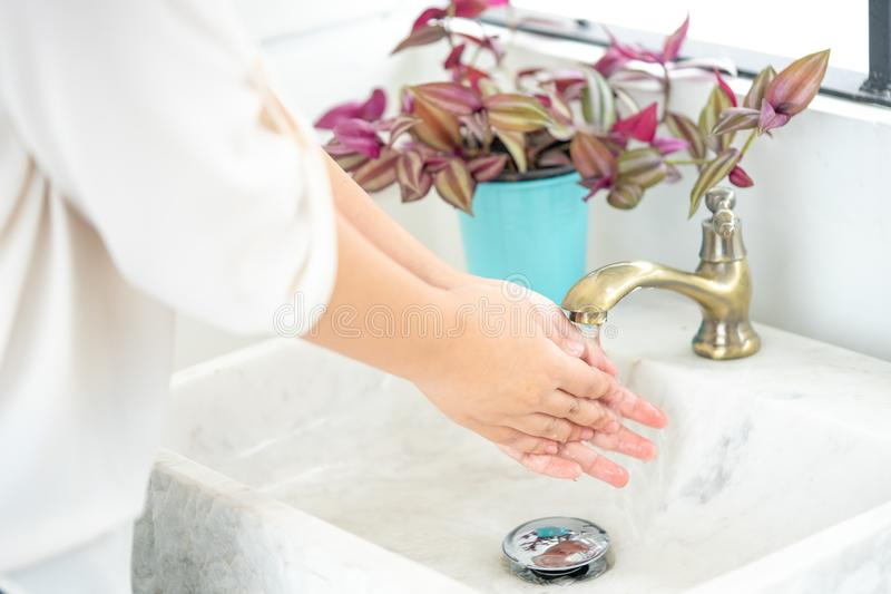 The woman`s hand is going to open the faucet to wash hands. To maintain cleanliness after entering the bathroom, the concept of stock photos