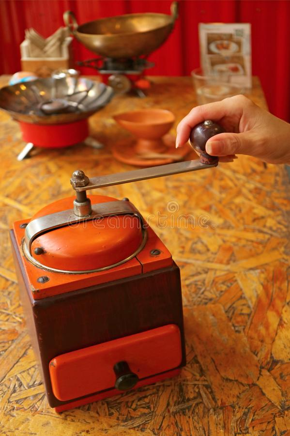 Woman`s hand grinding coffee beans in a vibrant color retro portable coffee grinder for homemade coffee royalty free stock images