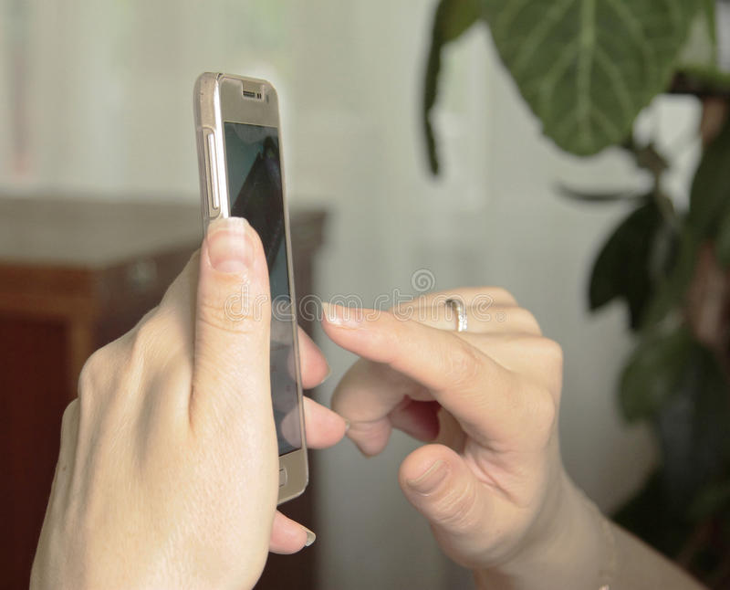 Woman's hand hold smartphone and touch a screen royalty free stock image