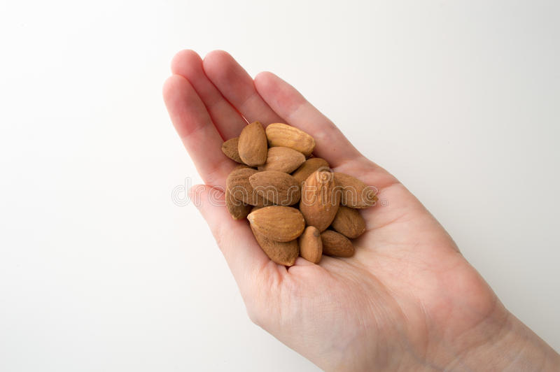 Woman's Hand Holding Almonds. On a White Backgound royalty free stock photo
