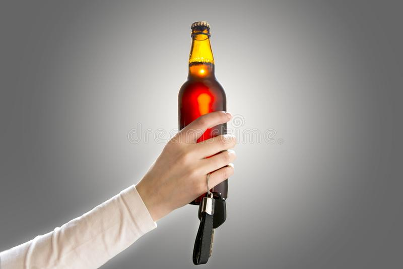 Woman`s hand holding bottle of beer and car keys. Do not drink a royalty free stock photos