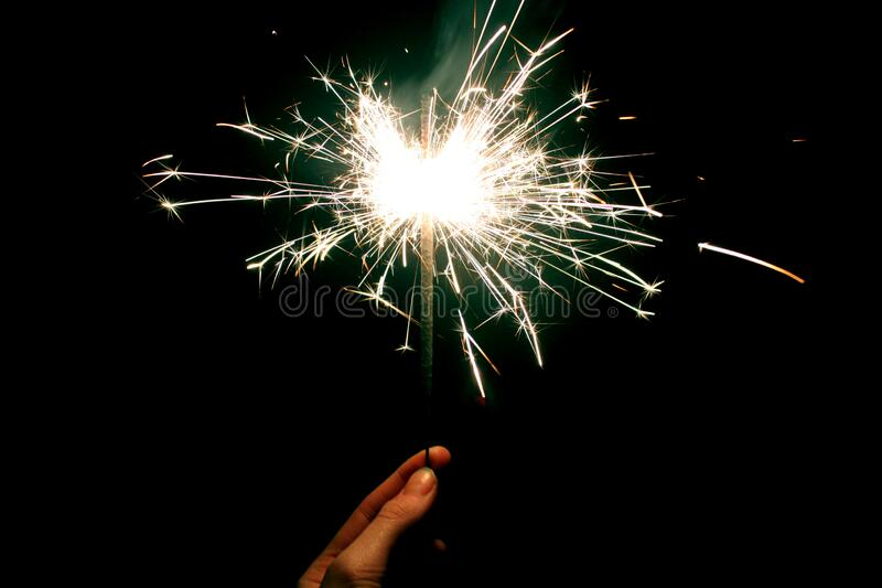 Woman`s hand holding burning Sparkler in hand in the dark on black background. Celebration concept. Woman`s hand holding burning golden color sparkler in hand in royalty free stock images