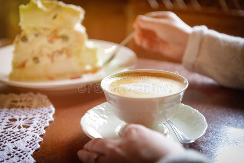 Woman`s hand holding cappuccino cup in the cafe royalty free stock images