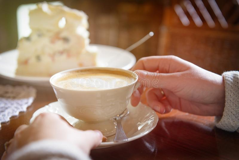 Woman`s hand holding cappuccino cup in the cafe stock photography