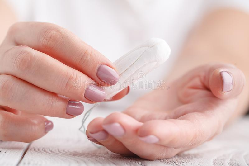 Woman`s hand holding clean cotton tampon close-up. Young woman p stock photos