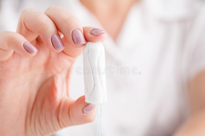 Woman`s hand holding clean cotton tampon close-up. Young woman p royalty free stock images